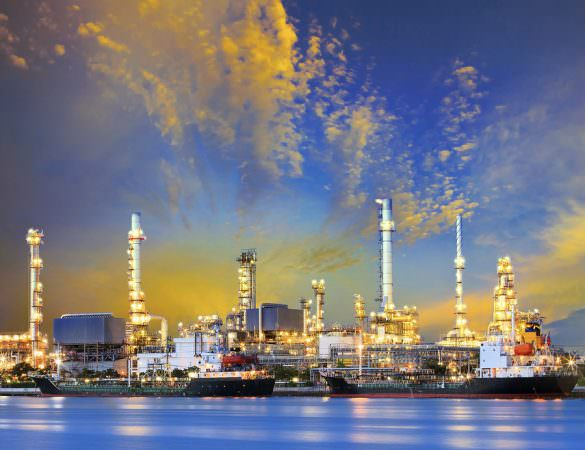 Shale companies thriving in a low price environment: tanker ship and petrochemical oil refinery industry plant with beuatiful lighting against dusky sky use for heavy industrial and energy fuel business