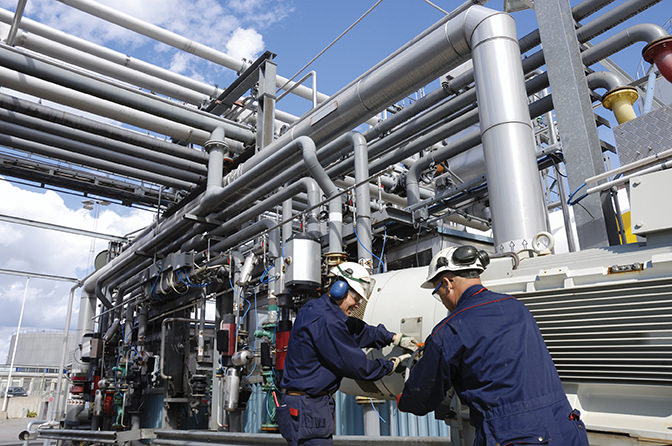 two oil and gas workers with pipeline machinery inside oil refinery - Mexico energy reform