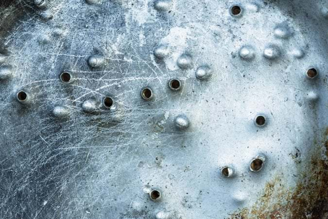 Holes from buckshot on metal surface - Metal surface with holes from bullets and shot
