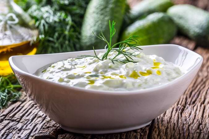 Tzatziki. Traditional greek dip sauce or dressing tzatziki prepared with grated cucumber sour cream yogurt olive oil and fresh dill. Mediterranean cuisine.