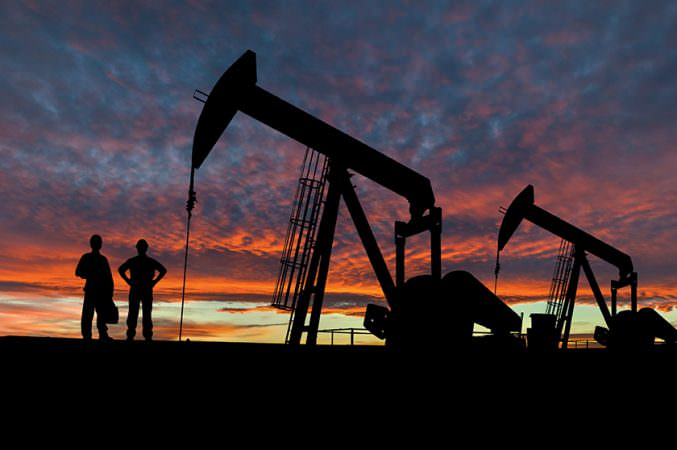 Silhouette of oil workers at an oil field pumpjack site against a dramatic sky.