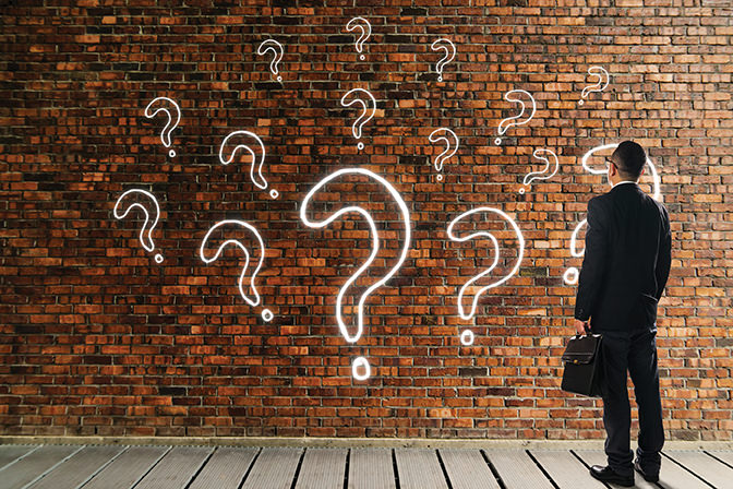 bigstock--184492282 - Businessman looking and thinking in front of a brick wall with the question marks icon . Business question concept .