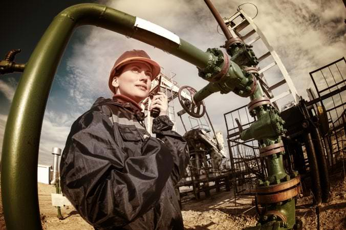 Female worker in the oil field talking on the radio wearing orange helmet and blue work clothes. Industrial site background. Toned.