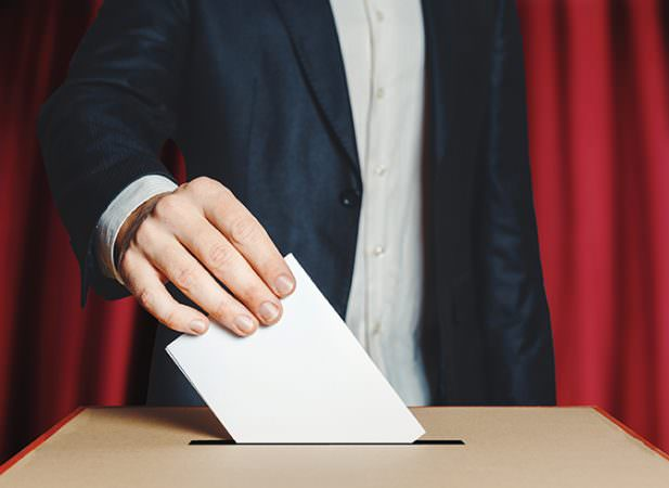 bigstock--222792166 Man Voter Putting Ballot Into Voting box. Democracy Freedom Concept On Red Background